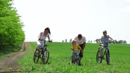 Family with children having a weekend excursion on their bikes. Father helping child learn to ride a bike