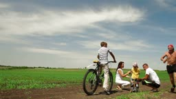 family with children having a weekend excursion on their bikes, senior man running.