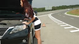 Attractive young woman looking under the car hood