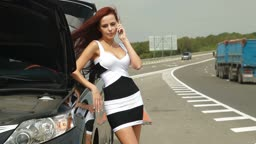Woman having car troubles on the road, calling on the cell phone for emergency repair service.