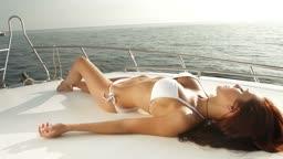 Attractive bikini woman sunbathing on luxury yacht