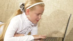 Blonde little girl using laptop at home
