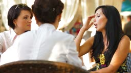 Female friends chat over a hot drink in outdoor cafe