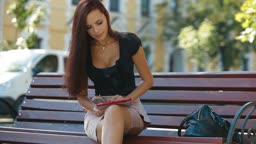 Attractive Woman Looking Photos on Digital Tablet Outdoors