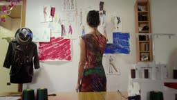 Young woman working as fashion designer contemplating drawings in studio