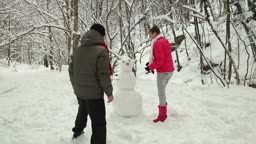 Teenage couple making a snowman in winter snowy forest