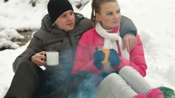 Young couple enjoying winter vacation near campfire in snowy forest