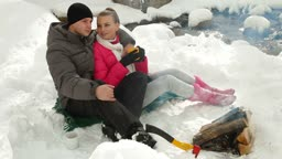 Young couple sitting by bonfire and drinking coffee in winter forest