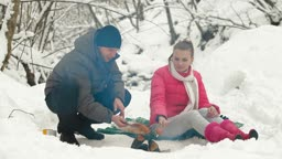 Young couple frying sausages on a fire in the winter forest