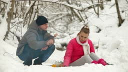 Young couple sitting by bonfire and roasting sausages in winter forest