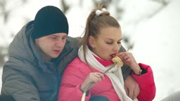 Teenage couple sitting by bonfire and roasting sausages in winter forest