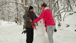 Young Couple Building Snowman In Winter Forest