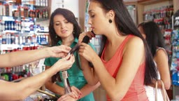 Sales Person Assisting Female Shoppers in Choice of Hair Dye