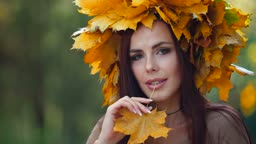 Young attractive woman enjoying autumn day in the park, looking at camera
