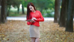 Young woman wearing red leather jacket with tablet computer in autumn park. Medium shot
