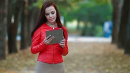 Young woman using tablet computer in autumn park