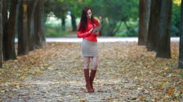 Young woman wearing red leather jacket using tablet computer in autumn park
