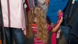 Little girl with her family shopping for clothes in a clothing store