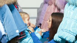 Mother and daughter shopping for winter clothes in a clothing store, child trying on down-padded coat