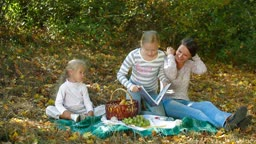 Young mother and two daughters enjoying autumn day at picnic in the park