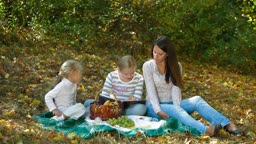 Young mother and two daughters enjoying autumn day at picnic in the park, child reading a book