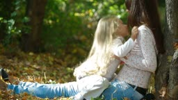 Young mother and little daughter enjoying autumn day in the park