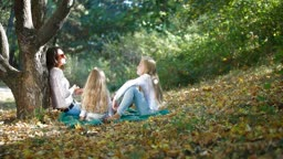 Cheerful mother with two daughters spending time together enjoying sunny autumn day