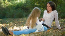 Young mother and daughter having a great day in the park, talking and laughing together