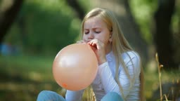 Child Blowing Up a Balloon Outdoors