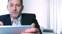 Businessman working with tablet PC ipad in his office or Hotel room - tracking shot