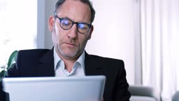 Businessman working with tablet PC / ipad in his office or Hotel room while screen reflects in his glasses - tracking shot