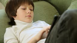 Teen Boy Using a Touch Screen Tablet PC At Home