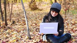 Teenager sitting on leaves with laptop in the park-Autumn.