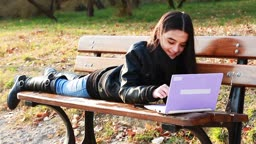 Teenager lying on bench with laptop