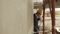 Engineer talking on mobile phone and walking in construction site