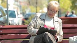 Active senior woman using digital tablet outdoors