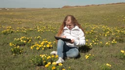 Little girl using a touch screen tablet PC on a meadow of wild peonies