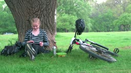 Girl cyclist using digital tablet computer in park
