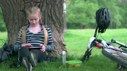 Teenage girl with bicycle sitting under tree, using tablet pc