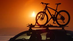 Cyclist attaching bikes to car roof carrier on summer beach at sunset