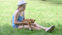 Child with puppy dog sitting on green lawn in summer day