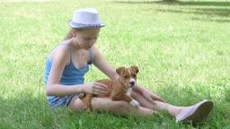 Little girl with puppy dog sitting on green lawn in summer day