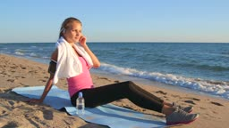 Fitness sporty woman in wireless headset relaxing after workout on the beach listening music from smart phone mp player
