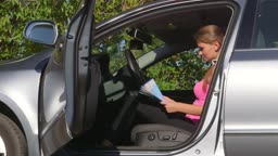 Young woman driver traveling by car looking at map for direction