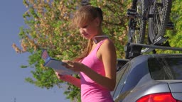 Young woman driver traveling by car with bicycle on roof looking at map