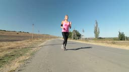 Fitness athletic girl jogging along the road during outdoor workout wide angle