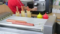 Employee making hot dogs and coffee cup in fast food lunch dinner