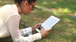 Young girl browsing her tablet laying on the grass in the park.Clerk chatting during her leisure time.Businesswoman sending message with tablet.Leisure typing woman an email on her iPad.