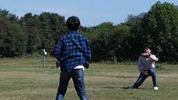 잔디밭에서 야구공을 주고 받는 아빠와 아들