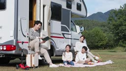 캠핑카 앞에서 아이들에게 책을 읽어주는 아빠